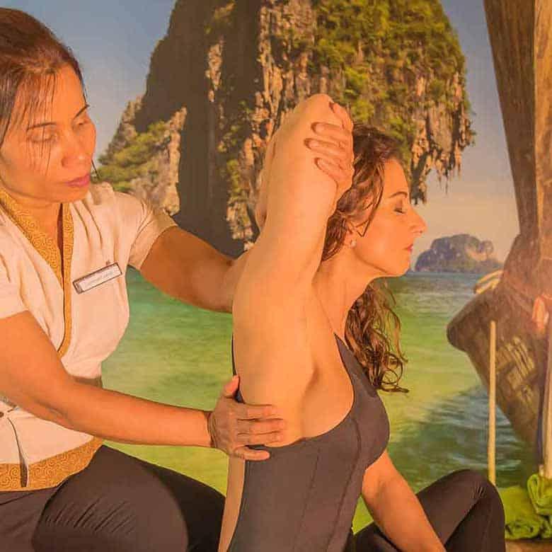 Masseurin dehnt vom Gast den Unterarm. Der Massage Raum ist gemütlich und erinnert an einen thailändischen Küstenabschnitt.