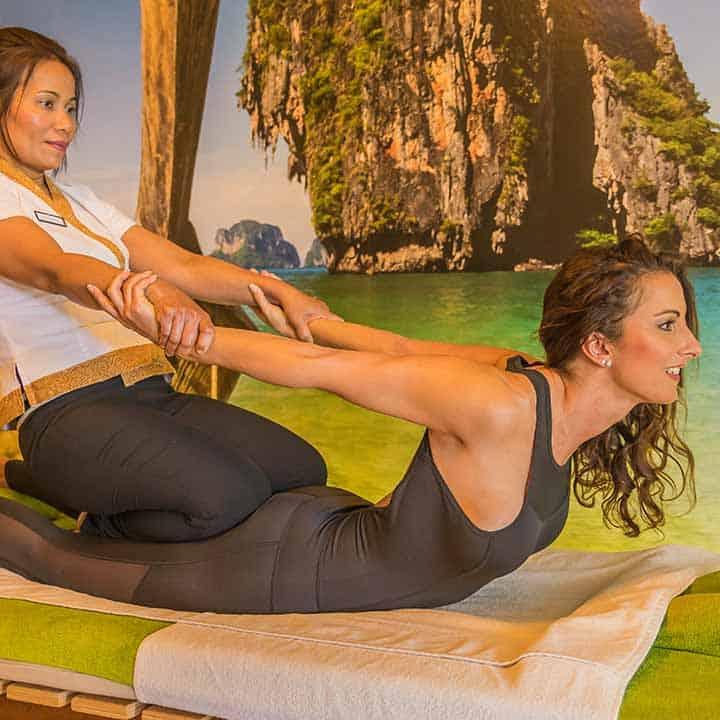 Gast wird bei der Thai Massage an beiden Händen in das Hohlkreuz gezogen um die Bauchmuskeln zu dehnen.