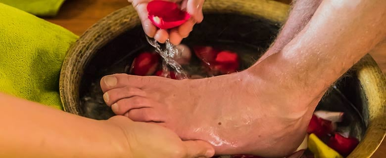 Die Füße stehen in der Wasserschale und werden für die Fußmassage im Massagepaket vorbereitet.