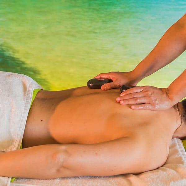 Die warmen Lavasteine werden mit der Hand während der Hot Stone Massage über den Rücken der Kundin geführt.