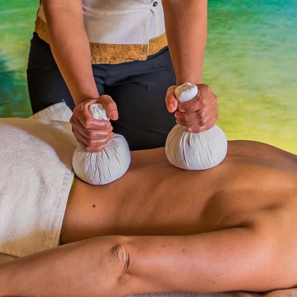 zwei Kräuterstempel werde zur Kräuterstempel Massage auf den Rücken gedrückt.