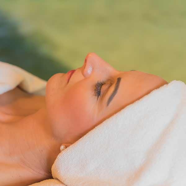 Für die Gesichtsmassage ist das weiße Handtuch um den Kopf gewickelt.