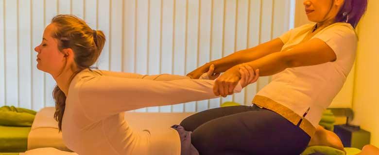 Masseurin zieht Dame während der Thai Massage in die Bauchstreck Position. Dabei sitzt sie mit den Beinen auf den Unterschenkeln des Gastes.