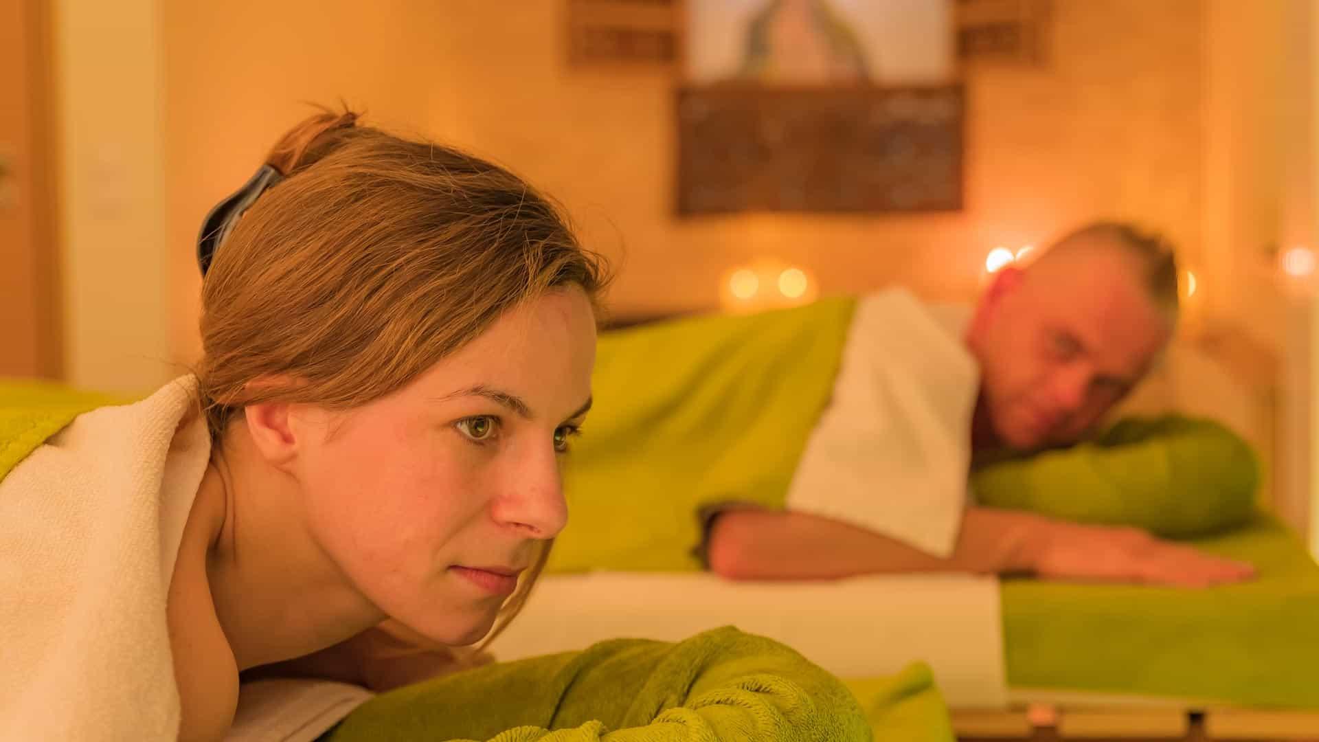 Synchron Partnermassagen: Frau und Mann sind bedeckt mit grünen Handtüchern und ruhen auf den Massageliegen im Massageraum