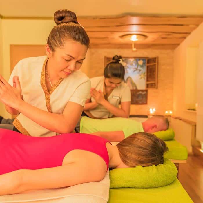 Frau im roten Shirt und ihr Mann im grünen Shirt auf der Massageliege werden mit der Synchron Partner Massagen von zwei Masseurinnen behandelt.
