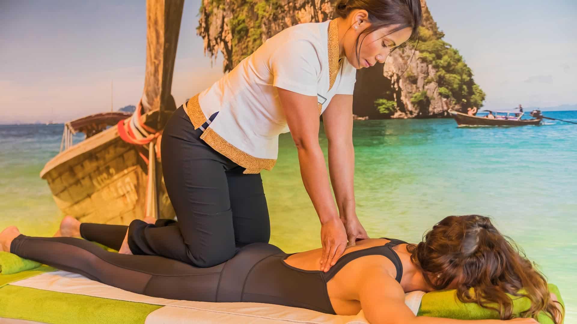bei der Thai Massage kniet die Masseurin auf dem Kunden und drückt mit den Daumen in die Schultermuskeln um Verspannungen zu lockern.
