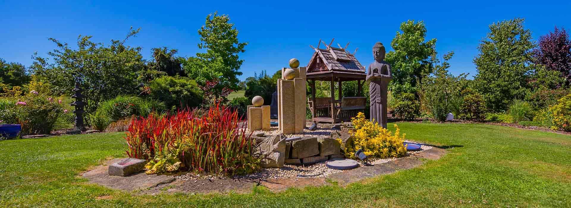 Park ähnliche Gruenanlage mit Buddha und Lavastein Skulpturen im LANAI green nature Spa