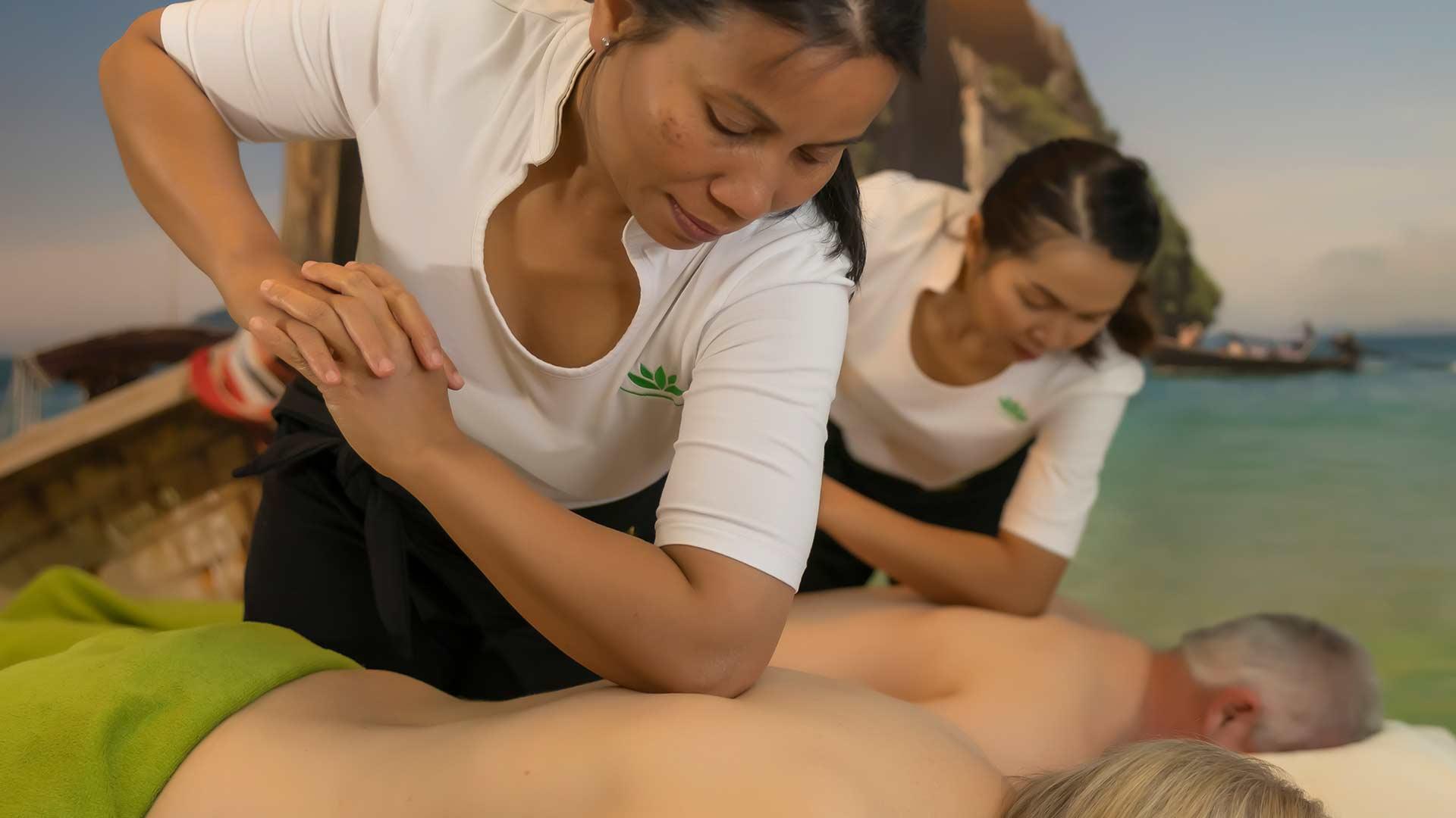 Zwei Masseurinnen drücken den Ellenbogen während der Thaimassage auf die Schulter.